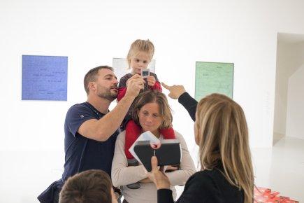 Une jeune fille sur les épaules de sa mère regarde une diapo, accompagnée de son père